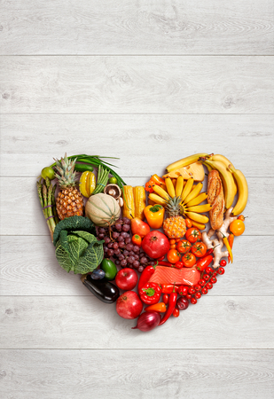 Foto de Heart symbol - food photography of heart made from different fruits and vegetables on wooden table - Imagen libre de derechos
