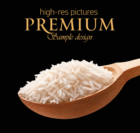Foto de Basmati rice in a wooden spoon - cereal on wooden spoons isolated on black background with place for your text - Imagen libre de derechos