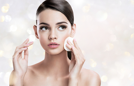 Photo pour Beautiful brunette woman removing makeup from her face, skin care concept - image libre de droit