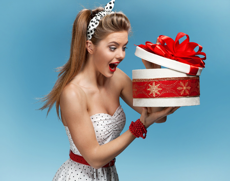 Photo pour Excited birthday girl opening surprise gift with a look of amazement and shock - image libre de droit