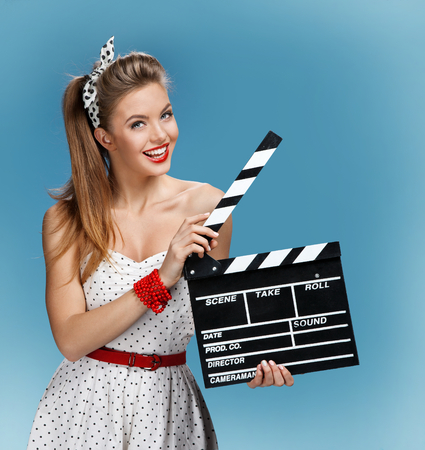 Photo pour pin-up girl holding a Clapper board. Filmmaking or film production concept - image libre de droit