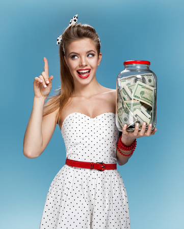 Foto de Retro woman with a jar of money having an idea How to Spend Money. Shopping concept - Imagen libre de derechos