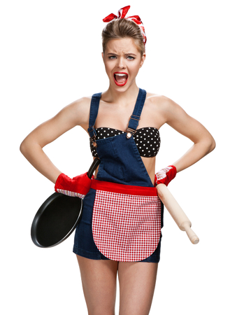 Photo pour Angry housewife with battledore and black frying pan / young beautiful American pin-up girl isolated on white background. Cleaning service concept - image libre de droit