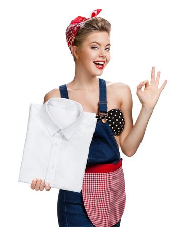 Photo pour Happy woman holding laundered white shirt and showing us it - image libre de droit