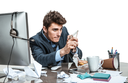 Foto de Concentrated man with slingshot aim  modern office man at working place sloth and laziness concept - Imagen libre de derechos