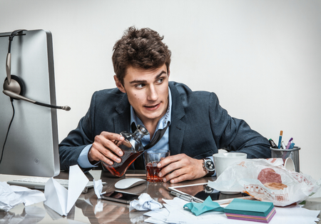 Photo pour Drunk businessman sitting drunk at office with computer holding glass looking depressed wearing loose tie in alcohol addiction problem concept - image libre de droit
