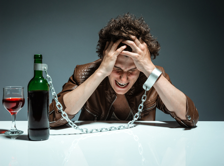Foto de Man in handcuffs interconnected with a bottle of alcohol  photo of youth addicted to alcohol, alcoholism concept, social problem - Imagen libre de derechos