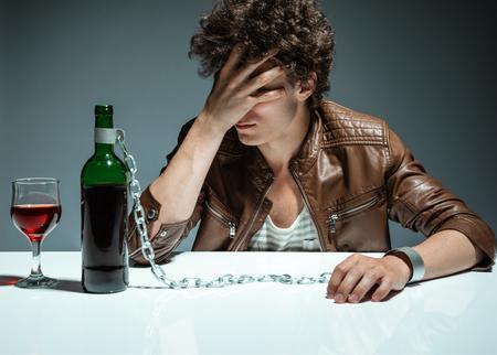 Foto de Sad and depressed young man in alcohol addiction  photo of youth addicted to alcohol, alcoholism concept, social problem - Imagen libre de derechos
