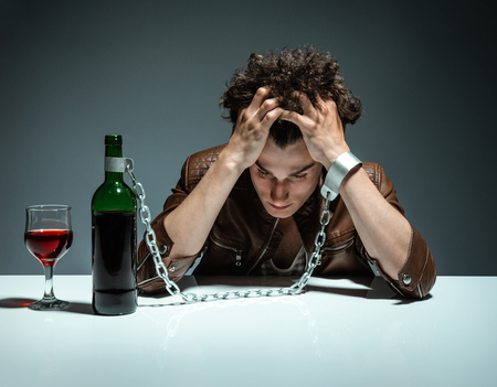 Foto de Intoxicated man sitting alone  photo of youth addicted to alcohol, alcoholism concept, social problem - Imagen libre de derechos