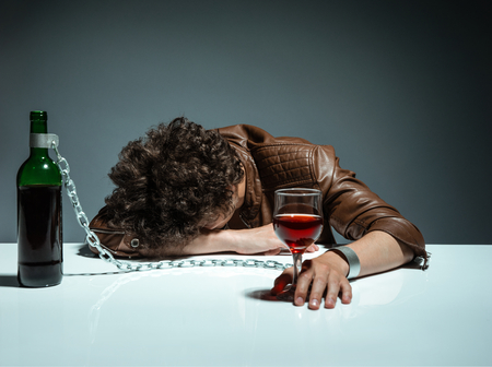 Foto de Young man passed out from alcohol  photo of youth addicted to alcohol, alcoholism concept, social problem - Imagen libre de derechos