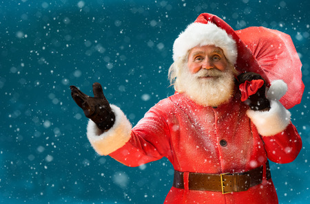 Foto de Real Santa Claus, carrying big bag full of gifts to children Merry Christmas New Year's Eve concept Closeup on blurred blue background. - Imagen libre de derechos