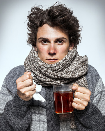 Foto de Man Cold Ill young man with red nose, scarf, sneezing into handkerchief. Medication or drugs abuse, healthcare concept - Imagen libre de derechos