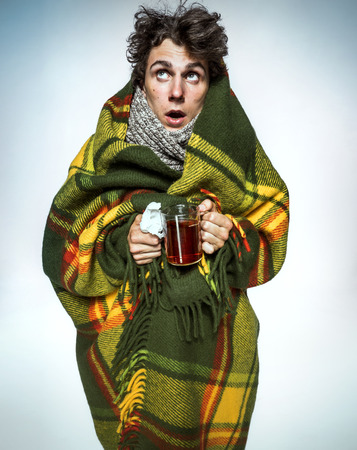 Foto de Ill Man covered with plaid blanket with hot tea sick man suffering cold and winter flu virus. Medication or drugs abuse, healthcare concept - Imagen libre de derechos