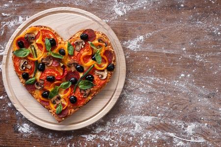 Foto de Baked heart-shaped homemade pizza on a cutting board on rustic table, close-up. - Imagen libre de derechos