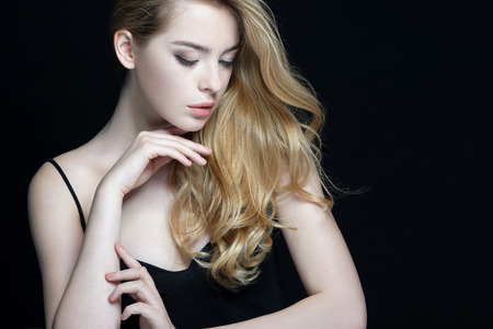 Beautiful woman touching her face, skin care concept. Close-up of an attractive girl of European appearance on dark background.