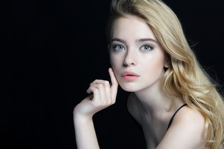 Photo pour Beautiful young lady with make up face. Close-up of an attractive girl of European appearance on dark background. - image libre de droit