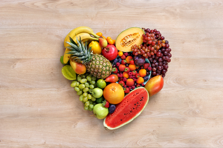 Photo for Heart symbol. Fruits diet concept. Healthy eating concept, food photography of heart made from different fruits on wooden table. High resolution product. - Royalty Free Image