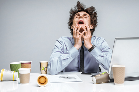 Foto de OMG! Frustrated man sitting desperate over paper work at desk. Negative emotion facial expression feeling - Imagen libre de derechos
