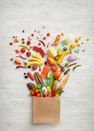 Foto de Healthy food in package. Studio photography of different fruits and vegetables on white wooden background, top view. High resolution product. - Imagen libre de derechos