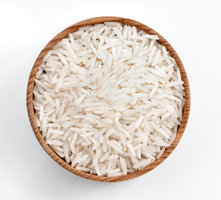 Foto de White rice in wooden bowl on white background. Close up, top view, high resolution product. - Imagen libre de derechos