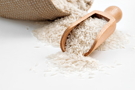 Foto de Raw long rice in wooden spoon and sack on white background. Close up - Imagen libre de derechos