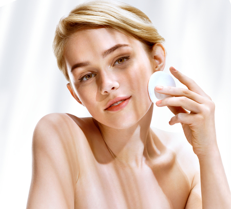 Photo pour Young woman cleaning skin by cotton pad. Photo of attractive blonde girl in sunny summer day. Youth and skin care concept - image libre de droit