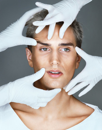 Photo for Facelift. Hands of doctors in gloves touching face of beautiful young man. Cosmetology concept - Royalty Free Image
