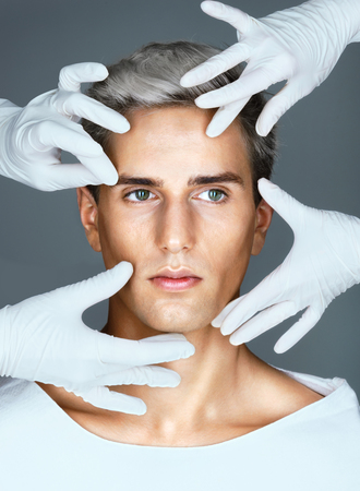 Photo for Facelift. Hands of doctors in medical gloves touching face of beautiful young man. Cosmetology concept - Royalty Free Image