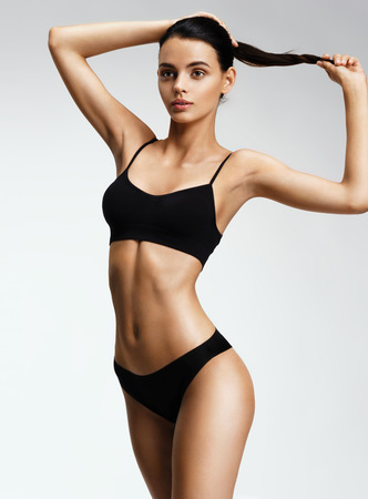 Photo pour Beautiful sporty woman in black bikini posing on grey background. Photo of girl with slim toned body. Beauty and body care concept - image libre de droit