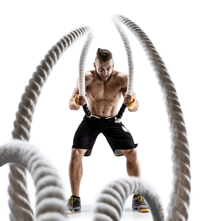 Foto de Attractive muscular man working out with heavy ropes. Photo of handsome man in sportswear isolated on white background. Crossfit - Imagen libre de derechos