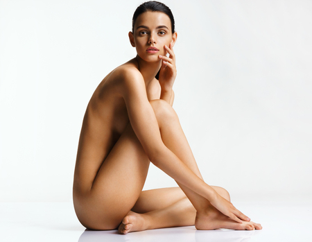 Foto de Beautiful girl with gorgeous figure sitting on white background. Photo naked girl sitting on the floor touch leg. Skin care concept - Imagen libre de derechos