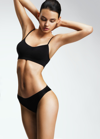 Photo pour Attractive sporty woman in black bikini posing on grey background. Photo of brunette woman with slim toned body. Beauty and body care concept - image libre de droit