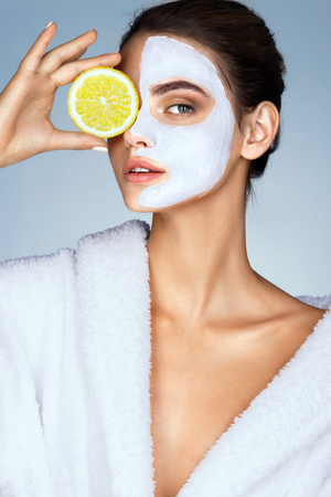 Photo pour Brunette woman holding a slice of lemon in front of her face. Photo of woman with moisturizing facial mask. Beauty & Skin care concept - image libre de droit