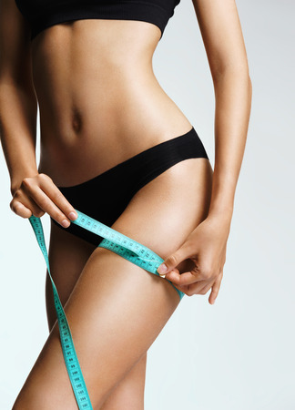 Foto de Sporty woman in black lingerie with tape measures the size of their hip. Beautiful part of female body. Fitness or body care concept - Imagen libre de derechos