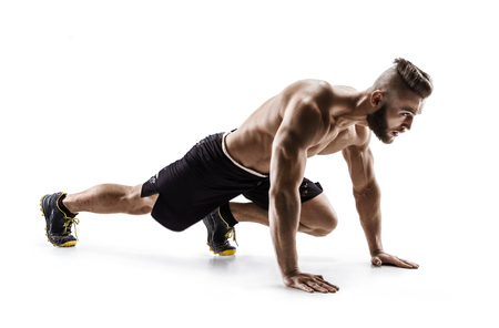 Foto de Young man doing stretching and warming up exercises. Photo of muscular man on white background. Sports - Imagen libre de derechos