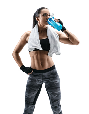 Foto de Resting time. Attractive young woman in sports wear and with towel on shoulders drink protein cocktail in special shaker. Health concept. - Imagen libre de derechos