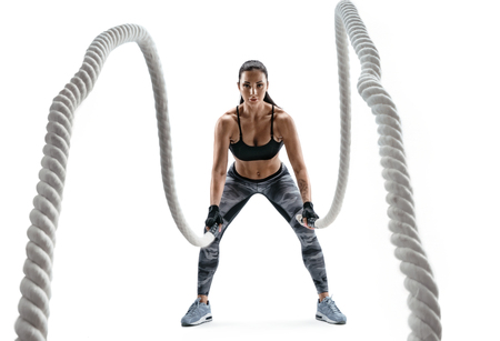 Photo for Strong woman working with heavy ropes. Photo of sporty girl in sportswear isolated on white background. Strength and motivation. - Royalty Free Image