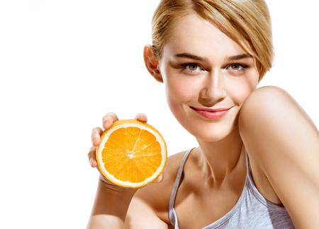 Foto de Smiling young girl holding oranges halves on white background. Great food for healthy lifestyle - Imagen libre de derechos