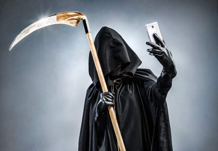 Foto de Grim Reaper making selfie photo on smartphone. Photo of personification of death wielding a large scythe in silhouette. - Imagen libre de derechos