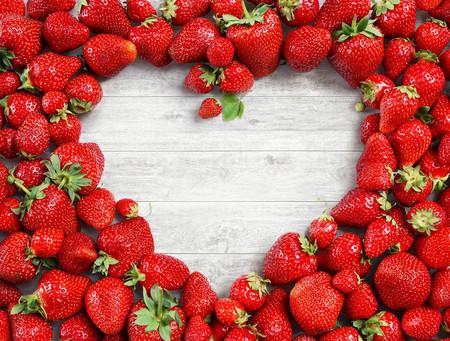 Foto de Heart shaped made of strawberry on white wooden background. Fruits diet concept. Close up. Top view. High resolution - Imagen libre de derechos