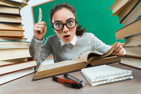 Foto de Did you know that?! Curious student reads a books. Photo of astonished young girl wearing glasses pointing finger up. Education concept - Imagen libre de derechos