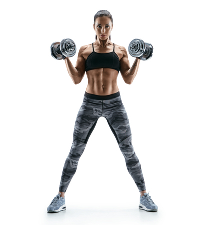 Foto de Beautiful young woman in training pumping up muscles of the back and hands with dumbbells. Photo athletic woman with perfect body isolated on white background. Strength and motivation - Imagen libre de derechos