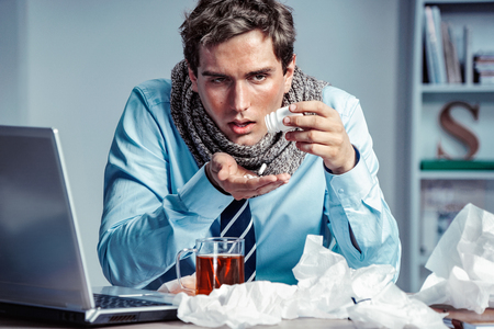 Photo pour Sick employee takes pills for flu in the office. Photo of young man suffering virus of flu. - image libre de droit