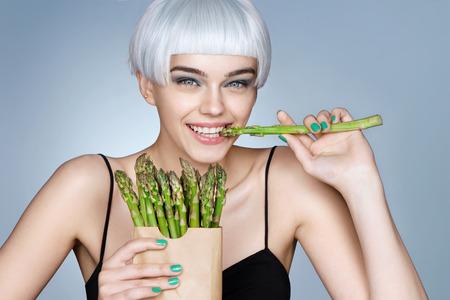 Photo pour Fashion girl with green asparagus. Photo of smiling blonde girl on blue background. Detox concept - image libre de droit