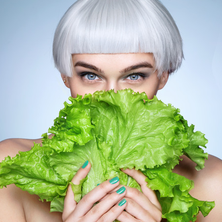 Photo for Pretty girl hiding behind a lettuce leaves. Photo of fashion blonde girl on blue background. Detox concept - Royalty Free Image