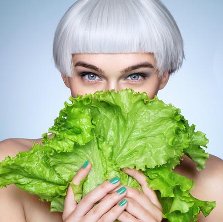 Photo pour Pretty girl hiding behind a lettuce leaves. Photo of fashion blonde girl on blue background. Detox concept - image libre de droit