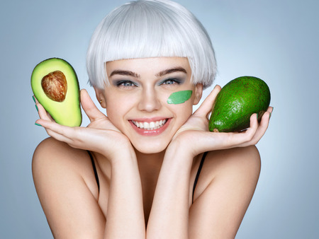 Photo pour Happy smiling girl with green avocado. Photo of smiling blonde girl on blue background. Skin care and beauty concept. - image libre de droit