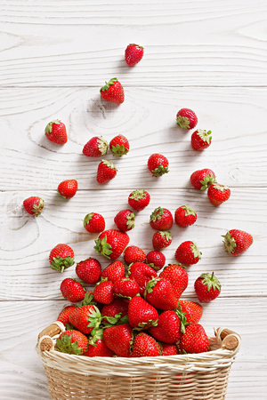 Photo for Strawberry explosion. Photo of strawberry in basket on white wooden table. Top view. High resolution product. - Royalty Free Image