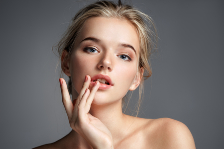 Photo pour Image with beautiful blonde girl touching her lips on grey background. Beauty & Skin care concept - image libre de droit