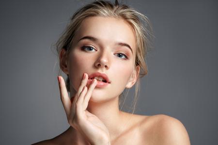 Foto de Image with beautiful blonde girl touching her lips on grey background. Beauty & Skin care concept - Imagen libre de derechos